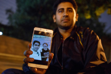 Pakistani businessman Mirza Imran Baig shows a picture of him and his wife Mailikemu Maimati as he sits outside the Pakistani embassy in Beijing