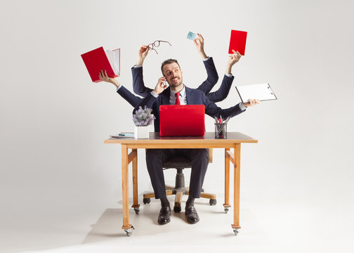 businessman with many hands in elegant suit working and holding office tools. Isolated over white background. Concept of busy