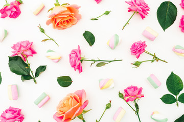 Round pattern of roses flowers and marshmallow on white background. Flat lay, top view.