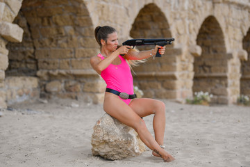 Beautiful sexy girl in a swimsuit and hat with a Winchester rifle seats on the ruins of an ancient city