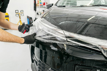 Car wrapping specialist putting vinyl foil or film on car. Protective film. Applying a protective film with tools for work. Car detailing. Transparent film. Car paint protection. Trimming.