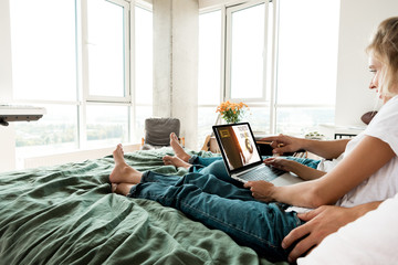 partial view of couple using digital laptop with tickets online lettering on screen while resting on bed at home
