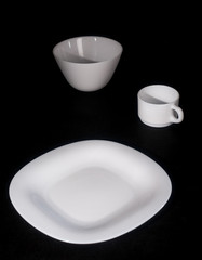 White plate with a mug on a black background