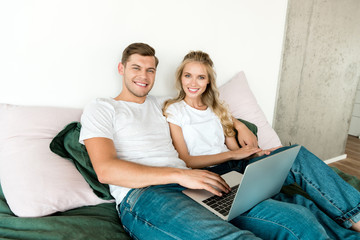 smiling young couple with digital laptop resting on bed at home