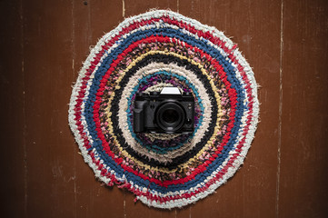 The camera is on a beautiful home round patterned carpet, lying on the brown floor at the entrance. Close-up.