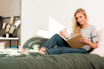 young smiling woman reading book on bed at home