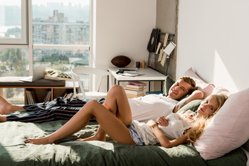side view of young couple in love in pajamas lying on bed in morning