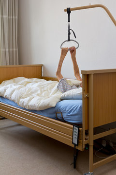 Old woman with a terminal illness trying to pull herself up with her extremely thin and weak arms on the gallow of the nursing bed in her hospice room.