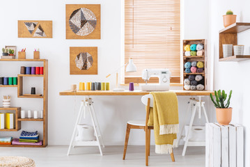 Real photo of a colorful room interior with a desk, sewing machine and threads