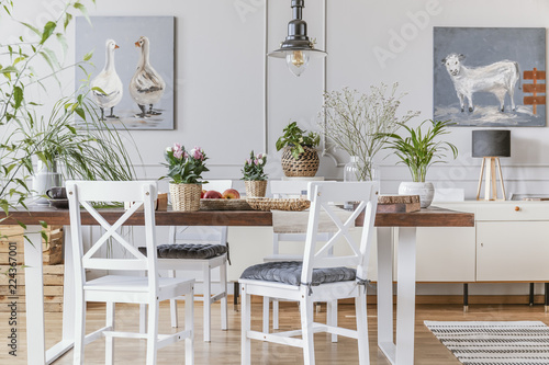White Chairs At Wooden Table With Flowers In Eclectic Dining Room