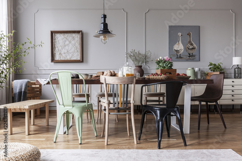 Lamp above wooden table with flowers in modern grey dining room