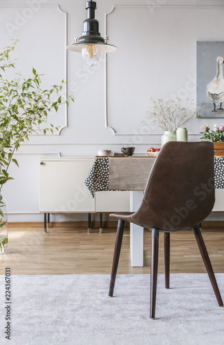 Black Chair On Grey Carpet At Table In Dining Room Interior With Lamp And Wall