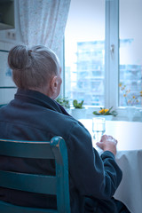 Loneliness concept, old-age depression: old woman sitting alone at her kitchen table looking out of the window, blue filter effect.