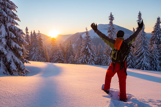 Adventurer stands with open arms in the winter mountains