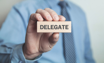 Businessman showing Delegate word in wooden block. Business concept