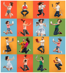 Jump of young women and man over colorful studio background using laptop or tablet gadget while jumping. Runnin people in motion or movement. Human emotions and facial expressions concept. Gadget in