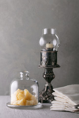 Parmesan cheese slices under a glass cap on a serving rack with an old candlestick and a stack of linen napkins. Still life in vintage style.