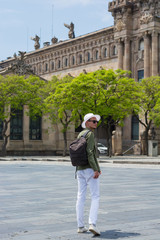 A young man in a hat, sunglasses walking in the port of Barcelona's at the port customs background, Barcelona, Spain