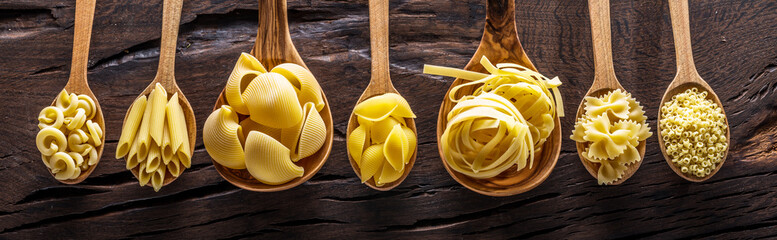 Different pasta types in wooden spoons on the table. Top view. Fotomurales
