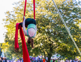 A woman is hanging upside down on a red ribbon
