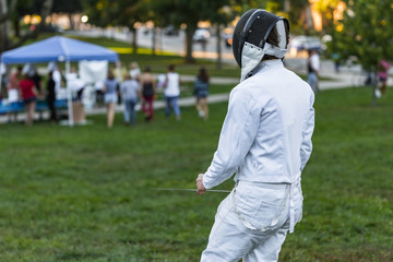 Fencing athlete on a green field