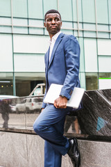Young Hansome African American Businessman traveling, working in New York, wearing blue suit, white undershirt, leather shoes, holding laptop computer, standing on street of Manhattan, looking away..