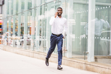 Hurry Up. Young African American businessman talking on cell phone, traveling in New York, wearing white shirt, blue pants, leather shoes, carrying laptop computer, running on street by glass wall..