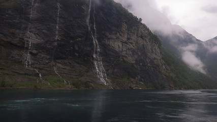 """The Seven Sisters or """"Dei sju systre"""" waterfall that lies directly across """"Friaren"""" or The Suitor waterfall, view from the fjord, at late afternoon, Geiranger Fjord, Norway"""