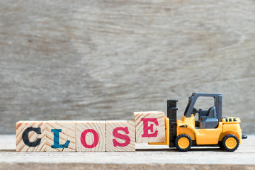 Toy forklift hold letter block e to complete word close on wood background