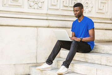 Young African American College Student studying in New York, wearing blue T shirt, black pants, sneakers, wristwatch, sitting on stairs outside office building, working on laptop computer on campus..