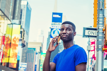 Young African American Man traveling in New York, wearing blue T shirt, standing on street in Times Square of Manhattan in summer, talking on cell phone. High buildings, billboards on background..