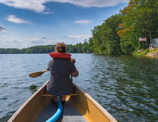 A woman is paddling in a canoe in a lake