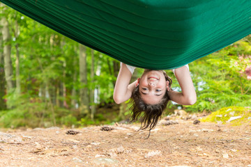 A girl is playing upside down in a green hammock