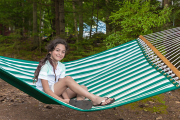 Young girl is sitting in a white and green striped hammock