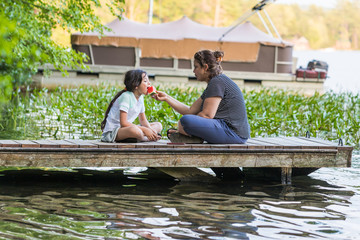 A woman is sharing a piece of watermelon with her young daughter while sitting on a dock