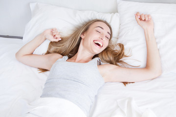 Happy, pretty girl waking up stretching arms on the bed in the morning. Rest,sleeping,people and comfort concept.