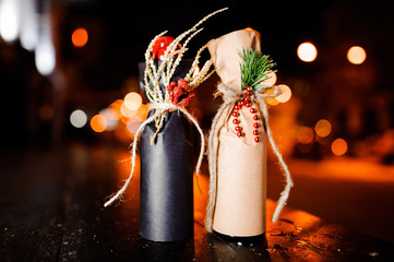 Two adorable christmas decorated bottles standing on the wooden bench
