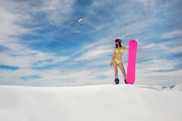 Young sexy girl in the yellow swimsuit with a snowboard standing on the snow cover