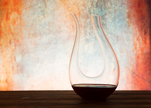 Stylish crystal U - Decanter with red wine on table