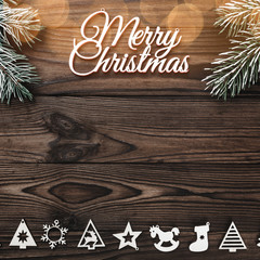 View from above of a Merry Christmas inscription and handmade tree toys and evergreen branch on wooden background, greeting card with space for text writing,  with light bulbs