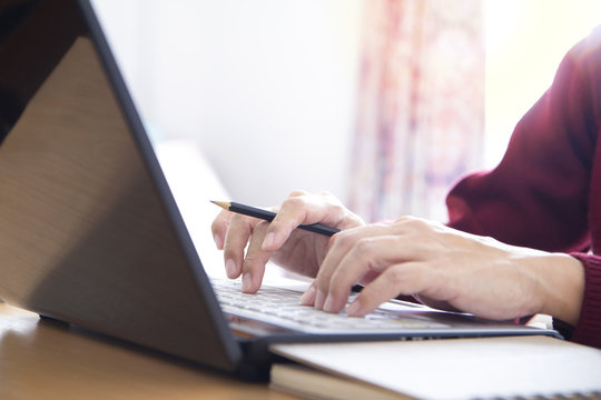 Hands of a man in red sweater holding a pencil while typing on laptop computer notebook keyboard in the office. Closeup with left and top copy space and easy to be cropped as a banner or strip.