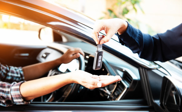 The remote car key was sending by lady hand to the driver hand,warm light tone,blurry light arond