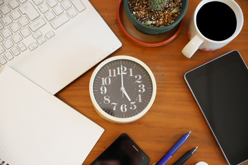 木目の机の上のパソコンとスマホと時計の仕事場