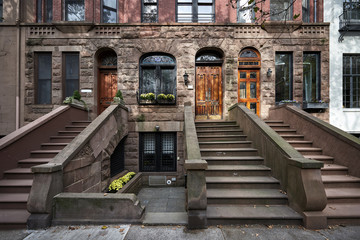 a row of colorful brownstone buildings in an iconic neighborhood  of Manhattan New York