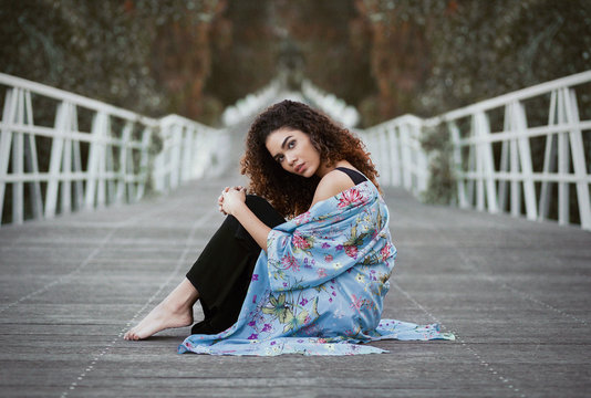 Attractive young woman sitting on footpath