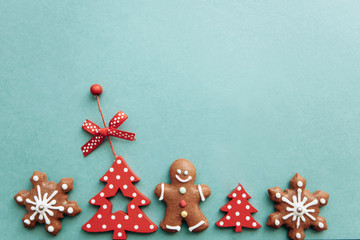 Christmas concept. Various Christmas toys, decorations and food including gingerbread cookies on a green background.