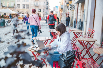 young adult woman working at laptop in outdoors cafe with cup of latte