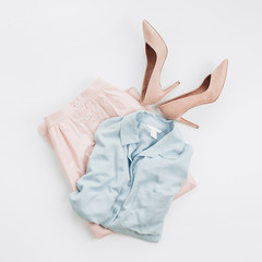 Woman pastel clothes: jeans shirt, skirt, high-heel shoes on white background. Flat lay, top view female fashion collage.