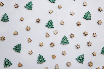 Small wooden Christmas trees and snowflakes. Festive decorated background. Christmas or New Year's concept in a minimalist style.