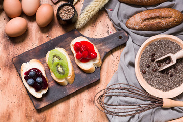 Freshly baked bread,eggs,blueberry cheesecake  and sesame on wooden table